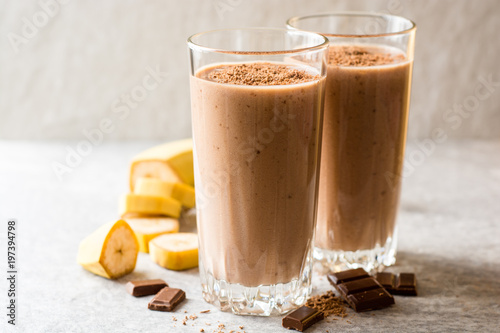 Chocolate banana smoothie in glass on gray stone background