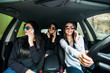 Three young women friends talking in the o car speak on phone