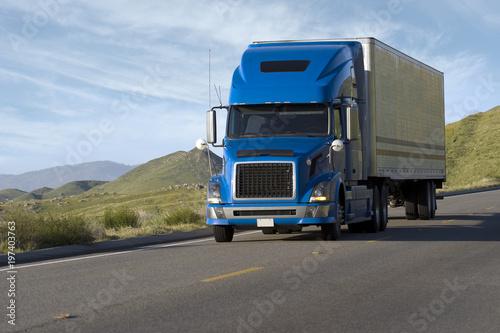 Fényképezés  Blue modern semi truck reefer trailer carry cargo on highway