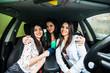 three girls driving in a car and having fun