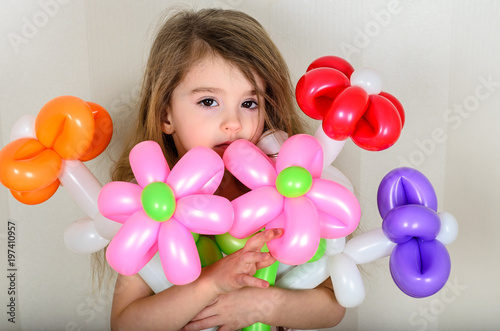 Photo  brown-eyed little girl hugs a bouquet of flowers from inflatable balls of red, o