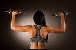 Active young woman wprkout with dumbbells in a fitness gym