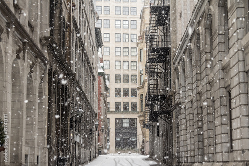 Street Alley of Old-Montreal in winter under a snow storm with a modern skyscraper in the background..