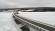 Aerial dolly of car driving on bridge over the frozen water in winter