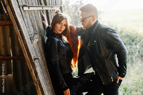 5c3a3639e stylish glamorous couple in black leather jackets posing in a hangar ...