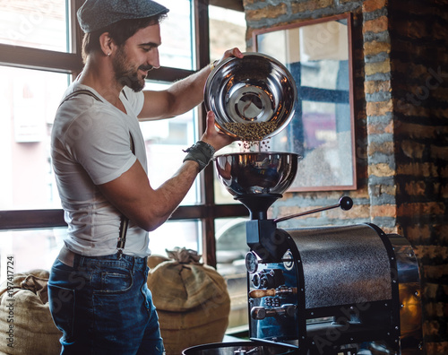 Fotografija Hipster pouring raw coffee beans in a coffee roaster