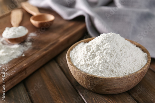 Wheat flour in bowl on wooden table Canvas Print