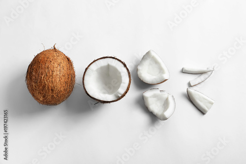 Pieces of coconut on white background, flat lay