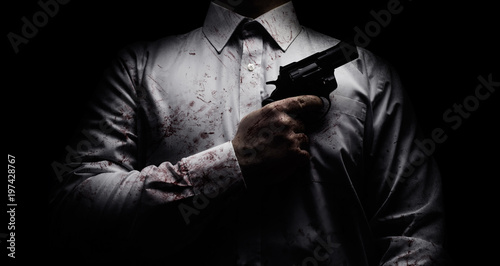 Fotografie, Obraz Horror scary photo of a killer in white shirt with blood splatter and posing with black gun on dark background