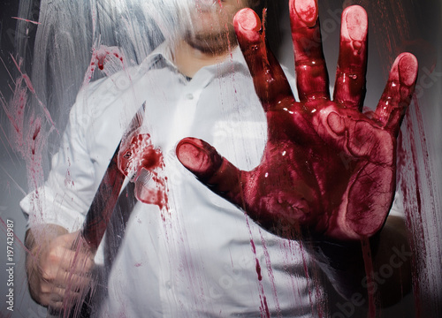 Photo Killer with bloody sharp big knife touching a glass with bloody hand