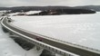 Aerial panning of a bridge over the frozen water in winter with cars