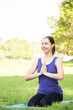 Beautiful woman doing yoga exercises in the park. Concept of healthy lifestyle.