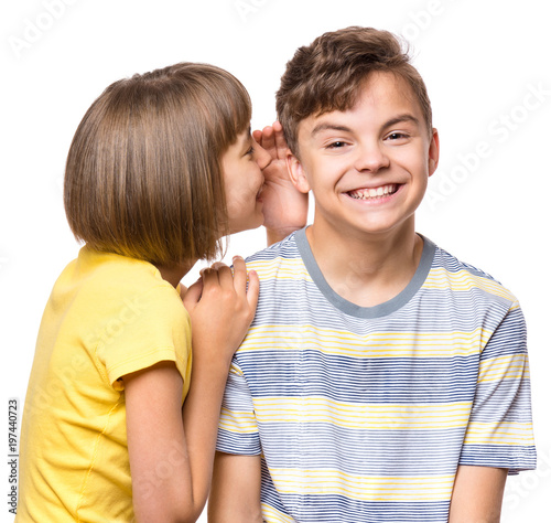 Photo Friendship - beautiful girl whispering something to teen boy
