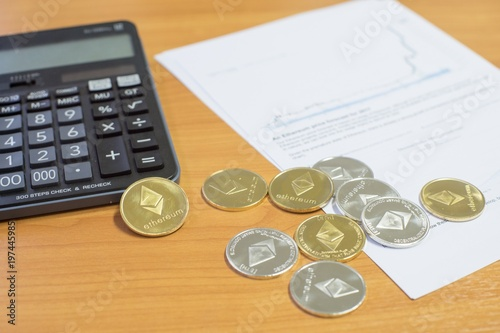 Gold And Silver Ethereum Coins On Brown Wooden Table With Calculator Increasing Graph The