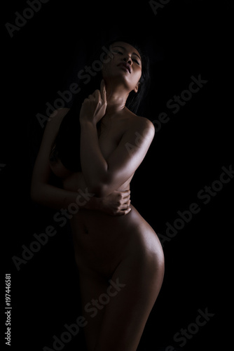 Deurstickers Akt Low key artistic nude of sexy young Asian woman standing on black background