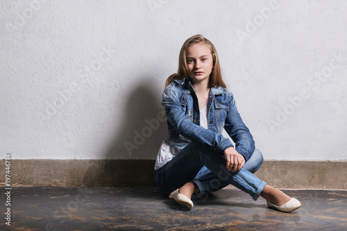 bc806966bf85 Girl near white wall. fashion hipster teen sits floor.Girl blonde ...