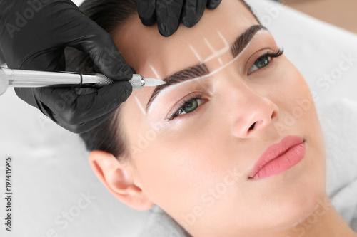 Obraz premium Młoda kobieta przechodzi procedurę makijażu permanentnego brwi w salonie piękności
