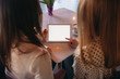 Two girls use a tablet while sitting in a cafe and drinking coffee
