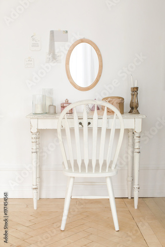 Leinwand Poster Interior shot of small boudoir dressing table with small mirror and white wooden chair