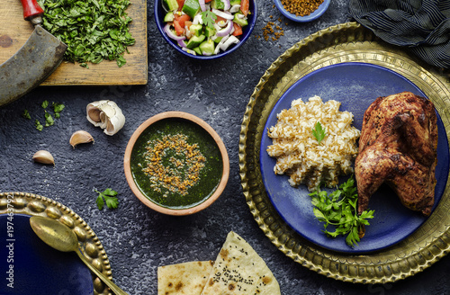 Arabic cuisine; Egyptian dish Molokhya or Molokhia placed with rice,chicken,pita bread,oriental green salad,crispy fried garlic and fresh ingredients on rustic background.