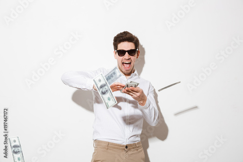 Fotomural Portrait of a happy young man in sunglasses throwing