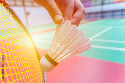 Obrazy Badminton   close-up-hand-hold-serve-badminton-shuttlecock-with-blur-badminton-court-background