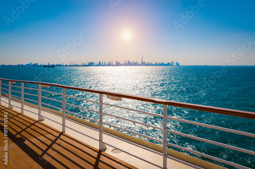 Railing of cruise ship with dubai skyline in the background.
