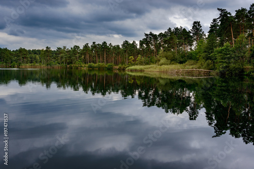 Ein dramatischer Wolkenhimmel spiegelt sich im Tonsee im Naturpark Dahme-Heidese Poster
