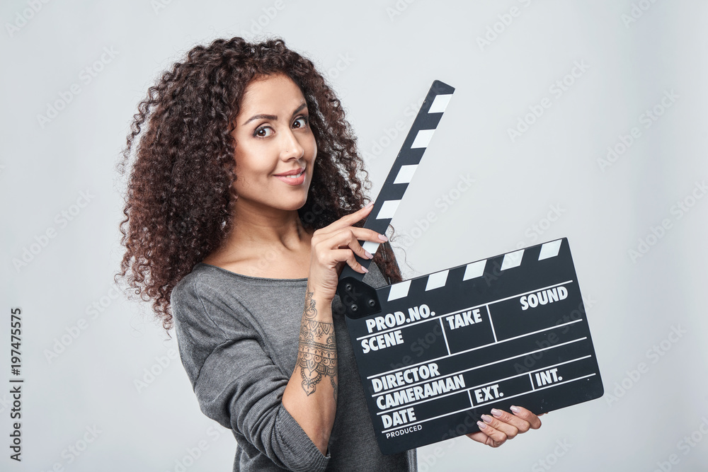 Photo  Smiling curly female holding movie clapper board, slate film.