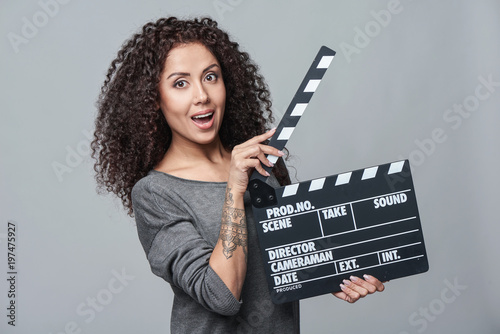 Smiling surprised curly female holding movie clapper board, slate film Canvas Print