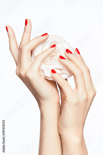 Fotografia Red Nails. Woman Hands With Flower And Red Manicure