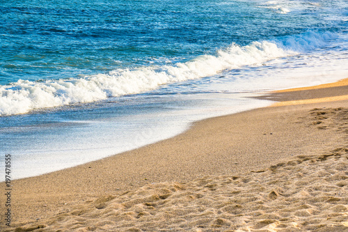 Beautiful beach with sand and blue water in the sun Canvas Print