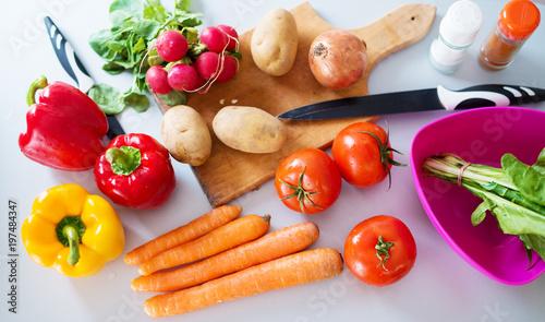 Fotodibond 3D Świeże różnorodne kolorowe warzywa są cięte i przygotowane do gotowania na blacie kuchennym.