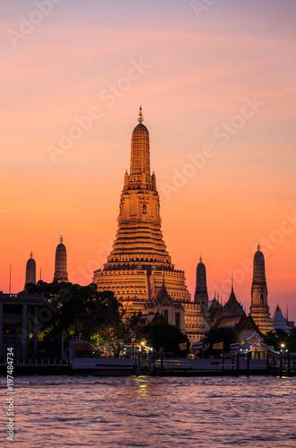 Photo le temple de wat arun au coucher de soleil le long de la chao praya à Bangkok