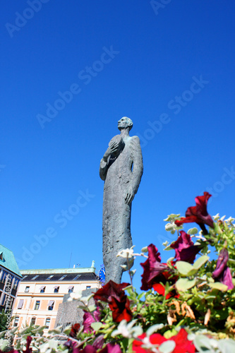 Statue of King Haakon VII of Norway in Oslo witrh flowers in a front Poster