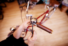 Close Up View Of Man's Hands Tightening Bicycle Bell Screws.