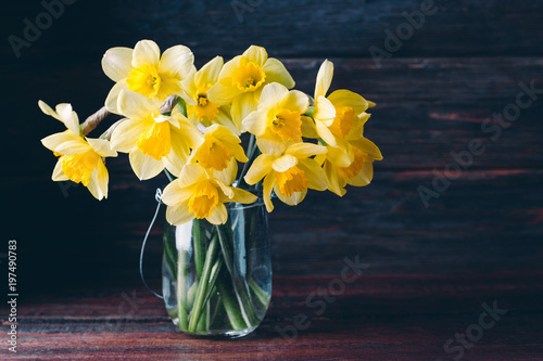 flowers daffodil in a glass vase on a wooden background