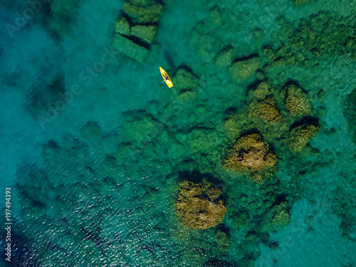 Aerial view of the paddle boat in the exotic turquoise coral sea.