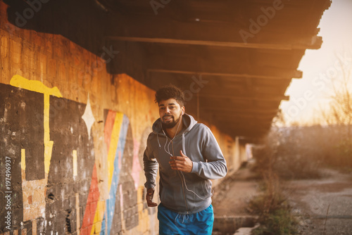 Fototapeta Portrait of active motivated afro-american young attractive athletic man with earphones running inside of the abandoned place. obraz na płótnie