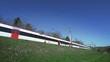 Wide angle shot of a train crossing the frame. Bright sunny day in the country side - national railway company