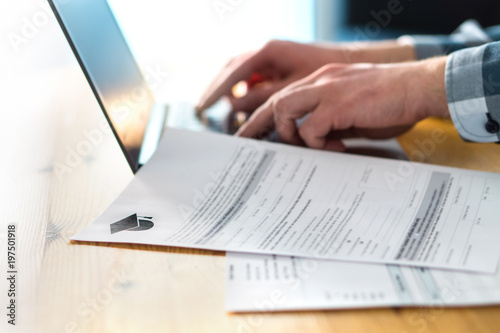 Fotografering  Young man writing college or university application form with laptop