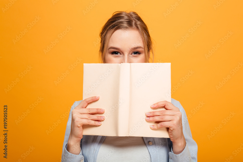 Fototapety, obrazy: Happy young lady student covering face with book