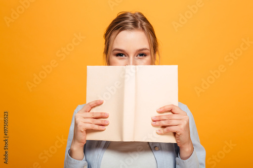 Fotografie, Obraz  Happy young lady student covering face with book