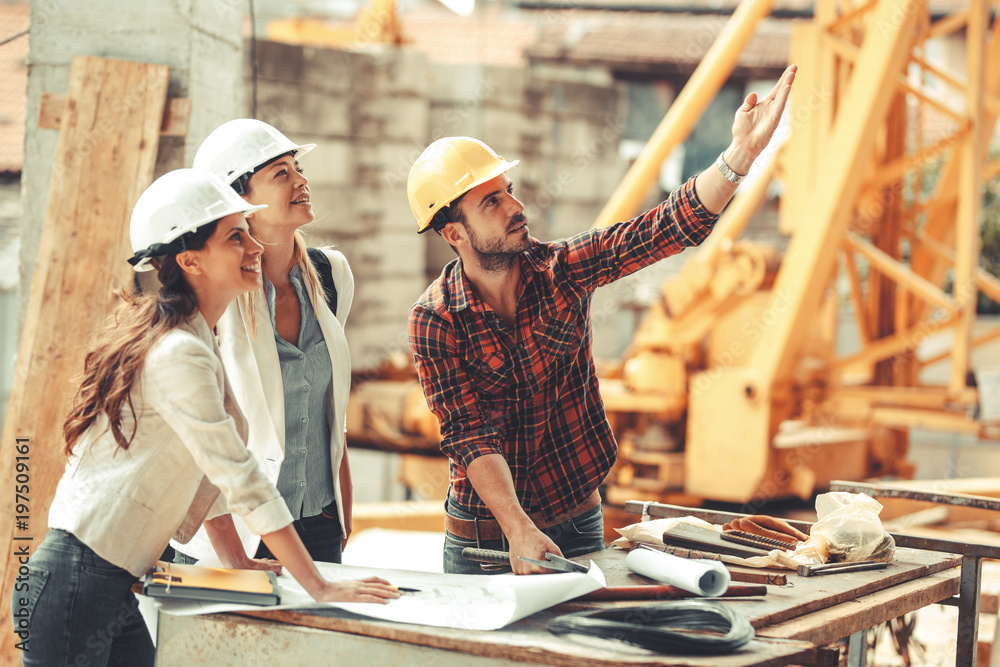 Fototapety, obrazy: Two female inspectors and architects discuss with head engineer about construction project.People at work concept.