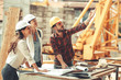 canvas print picture - Two female inspectors and architects discuss with head engineer about construction project.People at work concept.