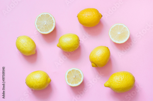 Fresh whole and sliced lemon on pink background. Flat lay.