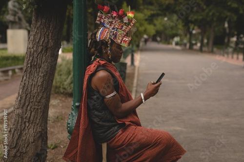 Maasai man in traditional clothing using mobile phone
