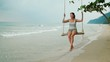Slow motion - happy woman relaxing on the swing at the beach during vacation in Thailand