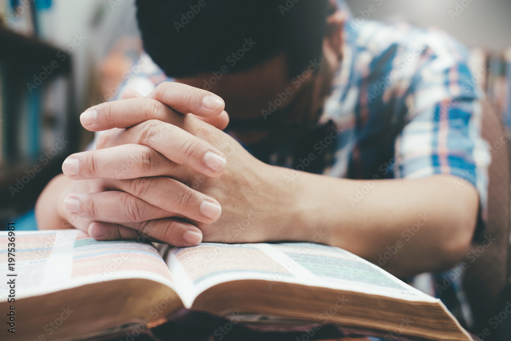 Fototapety, obrazy: Man praying, hands clasped together on her Bible.