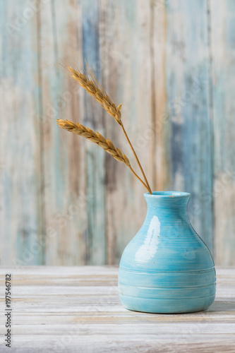 Fotografie, Obraz  Blue pottery vase with wheat against rustic wood background
